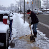Photo of a man sprinkling sand on an icy sidewalk by Anna I/sxc.hu.