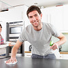 Photo of a man disinfecting a kitchen counter by omgimages/istockphoto.com.