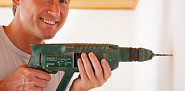 Photo of a man drilling with a power drill by nullplus/istockphoto.com.