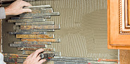 Photo of someone installing a tile backsplash by BanksPhotos/istockphoto.com