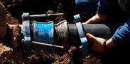 Photo of a sewer contractor working on a pipe by asterix0597/istockphoto.com.