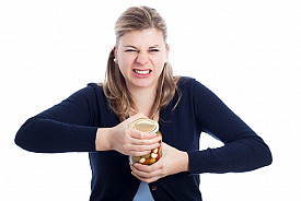 This lady is struggling to open a jar. Too bad she didn't read this article. (Photo: JanMika/istockphoto.com.)