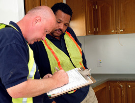 Inspectors stand before freshly installed cabinets in a FEMA trailer. Photo credit: Bicknell/FEMA.