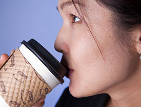 Photo of a woman drinking from a paper coffee cup by emyerson/istockphoto.com