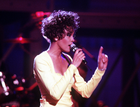 Whitney Houston performing for US troops in a televised concert. [Photo via Wikimedia Commons]