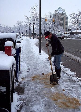 Photo of a man sprinkling sand on an icy sidewalk by Anna I/sxc.hu.