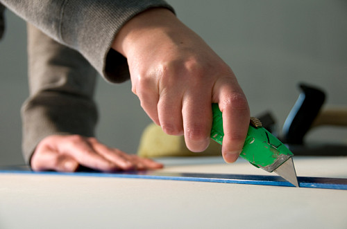 A worker cuts drywall with a knife.