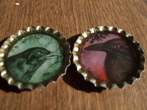 Photo of bottle cap magnets with painted ravens by JenHuff1/Flickr.